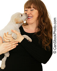 Puppy Kiss - caucasian girl playing with cream labrador...