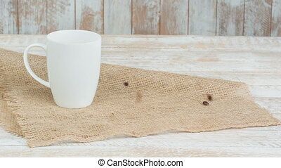 Cup of coffee and beans falling down beside it. - Average...