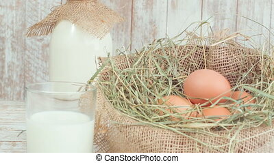 Milk and eggs in straw nest. - Farm products. Milk in...