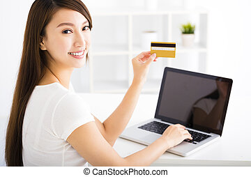 happy young woman showing credit card and laptop
