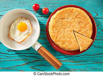 Egg over easy on white pan and potato omelette - Egg over...