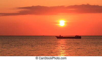 Boat Silhouette Drifts in Sea at Sunset against Orange Sky -...