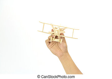 Hand holding a wooden airplane model isolated on white background