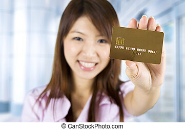 Credit card - Asian woman holding a credit card, focus on...