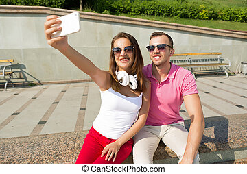 We love making selfie - Happy young loving couple making...