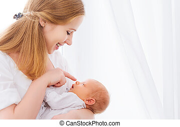 newborn baby in tender embrace of mother - newborn baby in a...