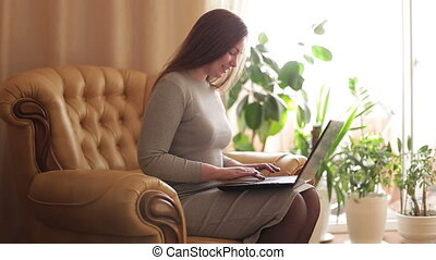 Businesswoman with a laptop working at home. Beautiful...