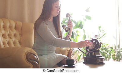 Beautiful young woman sitting on the couch dials a phone number and talking.