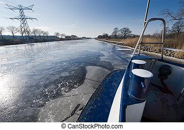 Icebreaker in Dutch canal breaks the ice in pieces