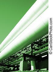 industrial pipelines on pipe-bridge against sky in green...