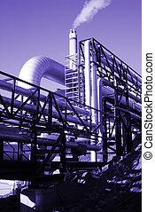 industrial pipelines on pipe-bridge against blue sky in blue...