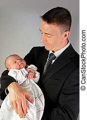 Baptism - 15 days old baby held by his Dad, wearing his...