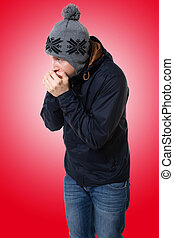 Man trying to warm up by blowing on his hands - A photo of...