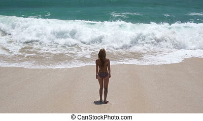 beautiful young girl on the beach is happy