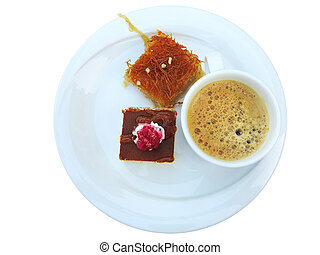 Coffee with Turkish sweets seved on white plate isolated