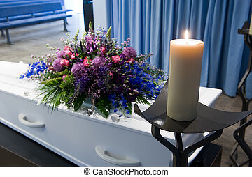 Coffin in mortuary - A coffin with a flower arrangement in a...