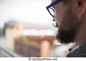Curled up mustache - Profile view of a bearded man with...