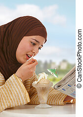 Newspaper and ice cream - Young veiled woman reading a...