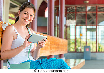 pretty woman with a tablet awaits the arrival of the train...