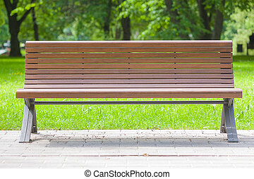 Bench in the summer park. Closeup, green grass