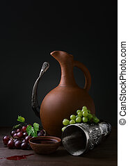 winemaking - cup of wine pitcher drinking horn and grapes on...