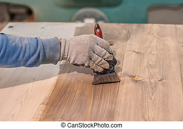 Paint Brush Staining - Young carpenter varnishing a wooden...