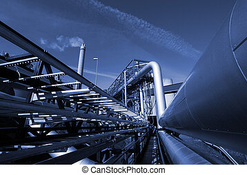 industrial pipelines on pipe-bridge against sky in blue tone...