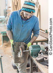 Carpenter Using Electric Sander - Carpenter sanding a wood...