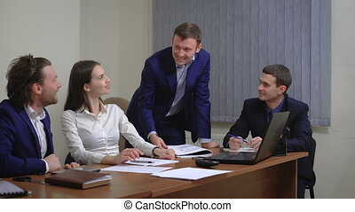 The team of young businesspeople. Rejoice success. In the office. The plan is executed.