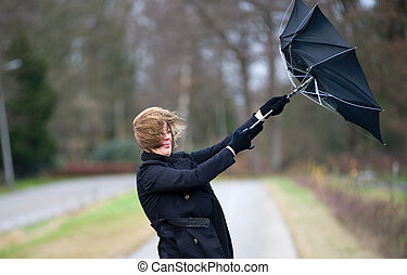 Fighting against the wind - A young woman is fighting...