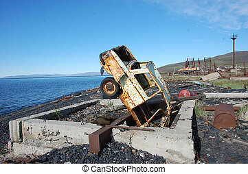Old broken rusty abandoned car upside down at sea coast,...