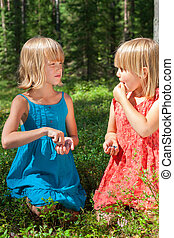 Children eating berries in a summer forest