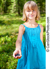 Girl shows picked berries in a summer forest shallow focus -...