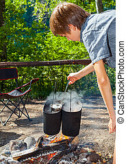 Child cooking on campfire - Young boy cooking camp food in...