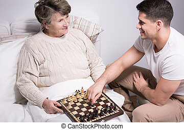 Playing chess with grandson - Older sick woman in hospital...