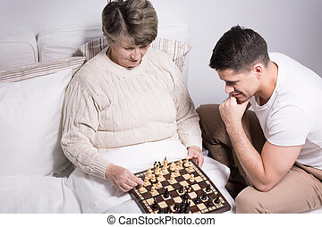 Man playing with grandmother - Young smart man playing chess...