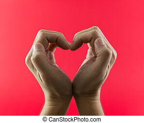 Hand in heart shape against red color background