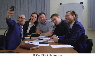Business people making face while taking selfie in office....