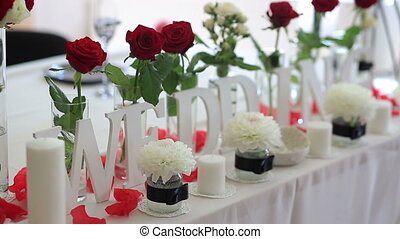 Table set for an event party or wedding reception decorated with red roses and white lilies