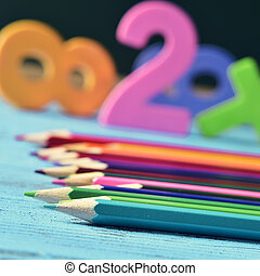 pencil crayons, and numbers on a blue wooden table - closeup...