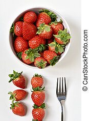 bowl with strawberries - high-angle shot of a white ceramic...