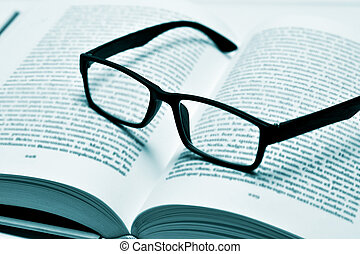 eyeglasses on an open book, in duotone - closeup of a pair...