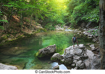 Man and spring lake in green forest