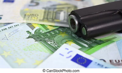 euro bills and gun - euro bills and black gun, close up