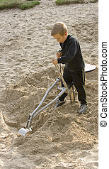 Sandpit - A boy plays on a toy digger in the sandpit at the...