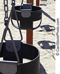 Empty Childrens Swing-set - Closeup of a black seat of a...