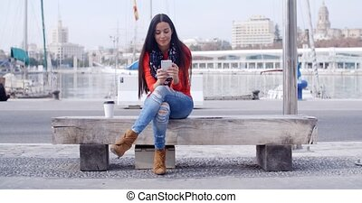Young woman sitting on a bench in town checking her mobile...
