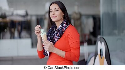 Attractive young woman eating an ice cream cone outdoors in...