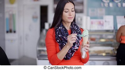 Smiling young woman savoring an ice cream cone - Smiling...