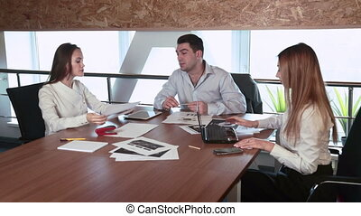 Negotiations in the office three people near by the table